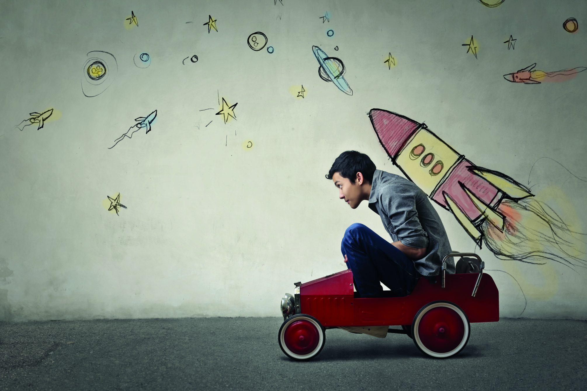 Mann auf Spielzeugauto mit Rakete auf dem Rücken